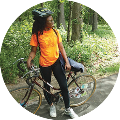 A young african-american woman stands next to her bicycle, facing the viewer but looking off to her left. She is wearing an orange shirt, black leggings, white sneakers, glasses, and a bike helmet.