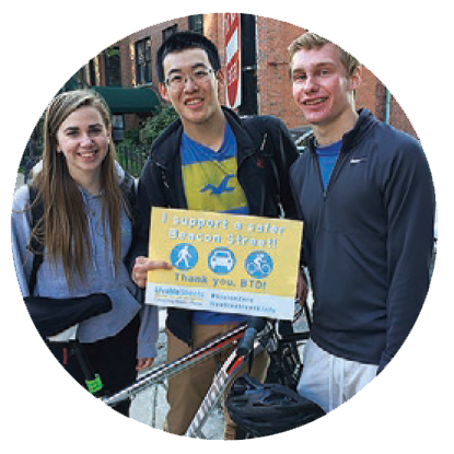 Three young adults, a caucasian woman with long straight brown hair, an asian-american man with short hair and glasses, and a caucasian man with blond hair, stand around a bicycle; the man in the center holds a sign that says \