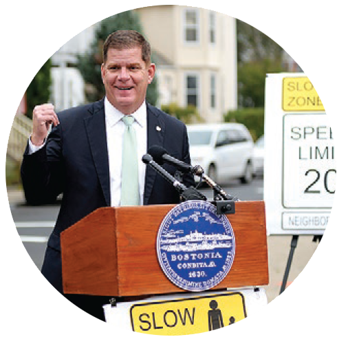 Mayor Walsh (a middle-aged caucasian man with greying brown hair) stands behind a podium surrounded by road signs that say \