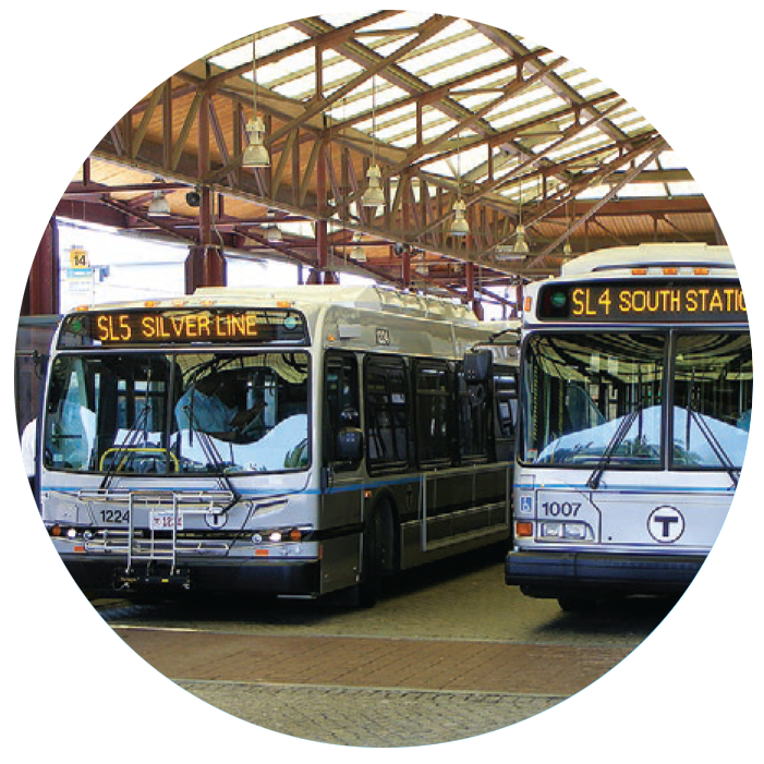 Two silver line buses sit in a sheltered bus stop