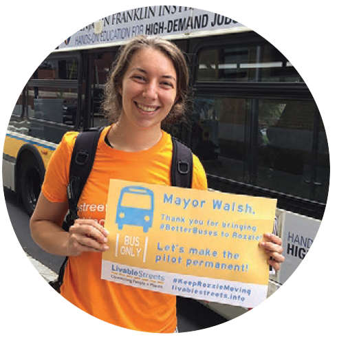 "A young caucasian woman with light brown hair, wearing an orange LivableStreets shirt and a backpack, holds a sign saying ""Mayor Walsh: thank you for bringing #BetterBuses to Rozzie. Let's make the pilot permanent!"" On the sign is an image of a bus in a ""bus only"" lane"