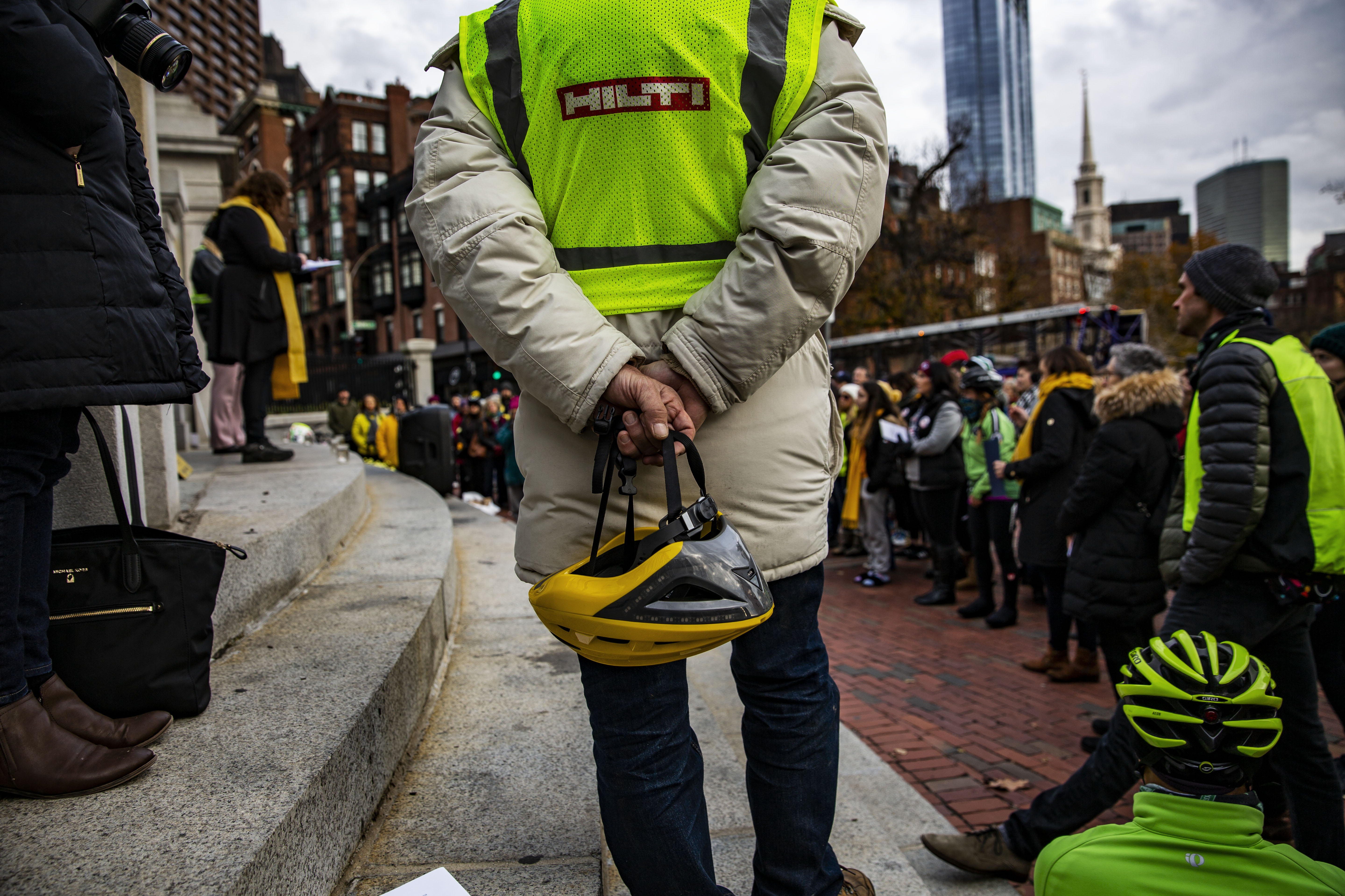 A crowd of people, many of whom are wearing yellow scarves or flourescent yellow vests, stand crowded around the steps of the Massachusetts State House in Boston. A woman with curly brown hair and a black jacket stands at the top of the steps and reads from something she is holding. Directly in front of the camera is the back of someone wearing a down coat and a yellow safety vest and holding a yellow bike helmet behind their back.