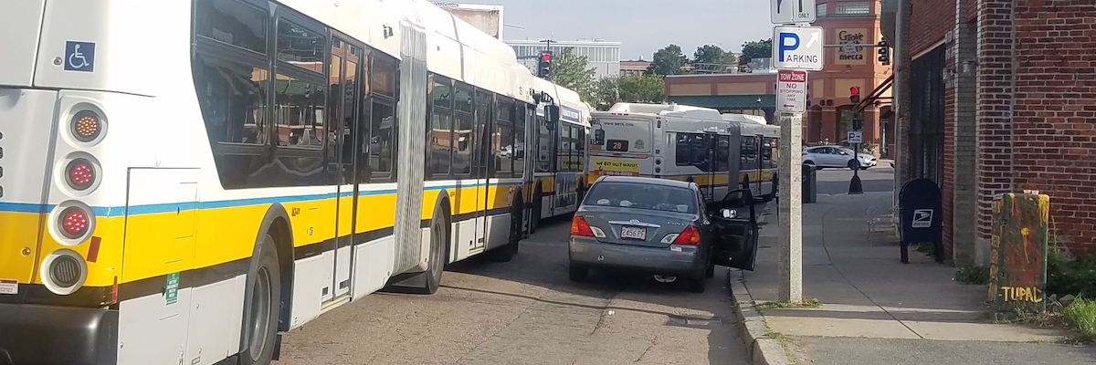 A line of buses drive past a car that is parked in a no parking tow zone.