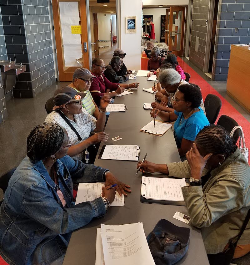 A dozen elderly Black people side on either side of a long table; some are talking, others are listening, and a few are looking at the papers and clipboards in front of them on the table.