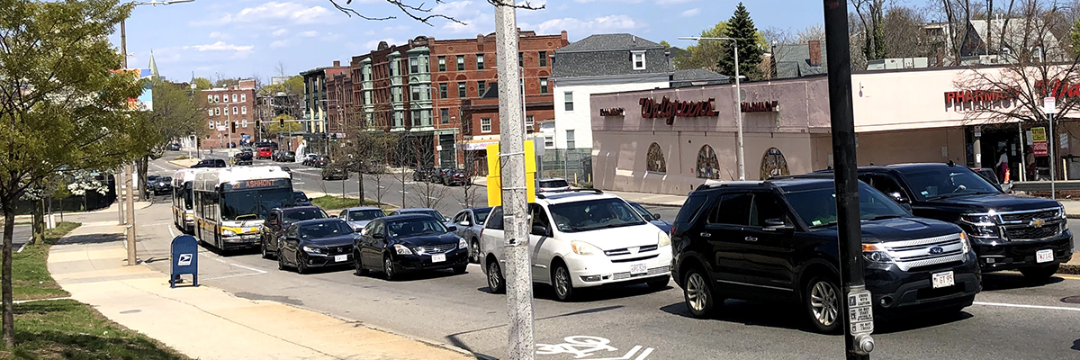 An image of Warren St, with two lines of cars stuck in traffic. Multiple buses are stuck behind the line of cars; meanwhlie, there is enough space by the curb for a bus stop and a bike lane that could serve as a bus-bike only lane.