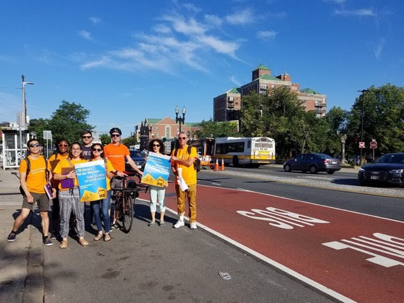 A group of Street Ambassadors, about half a dozen people, smile at the camera. They are wearing orange shirts, two hold blue and orange signs, and they are standing in an empty parking lane next to a red bus-bike only lane.