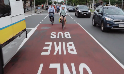A photograph of the bus-bike lane, with three cyclists riding along it towards the viewer, with cars on their left and a bus on their right.