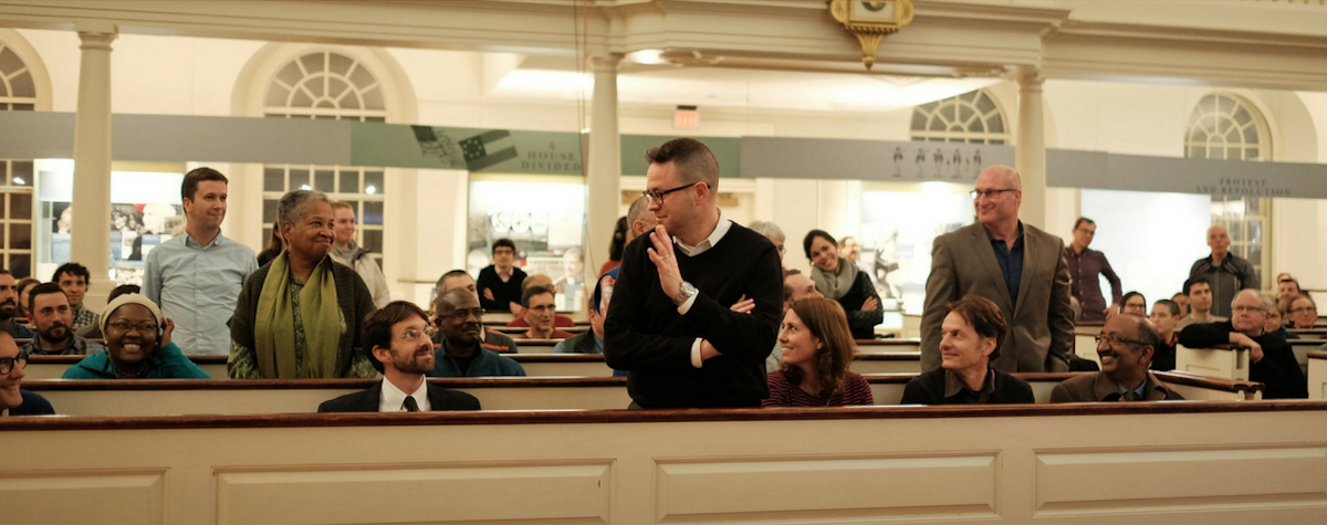 The StreetTalk audience sit in pews; some stand up as others look at them smiling