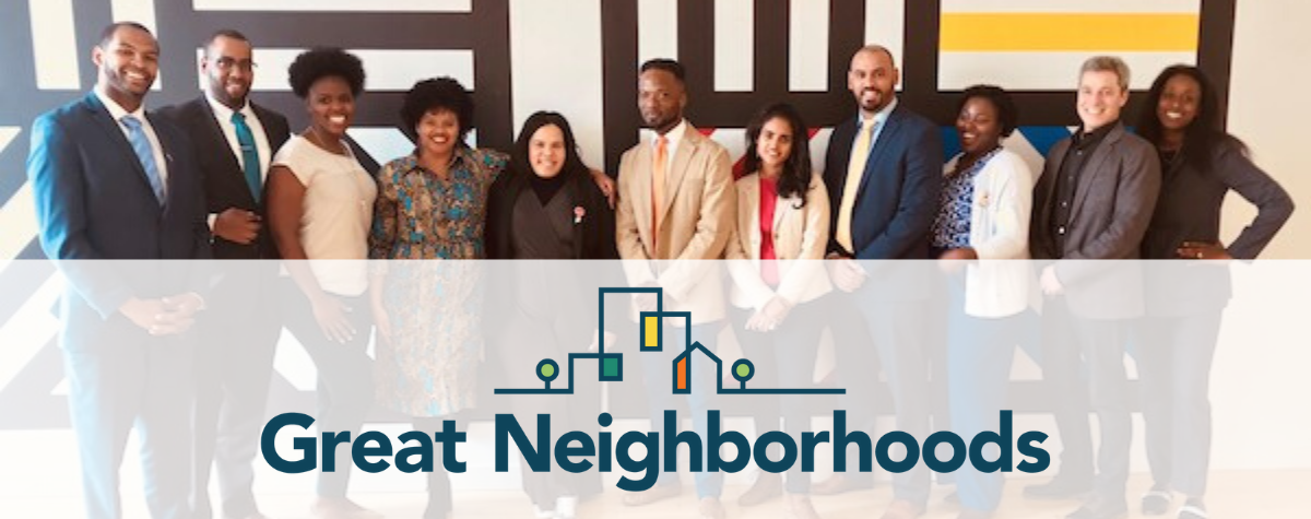 A line of people, featuring Great Neighborhoods program director Anabelle Rondon in the center, standing in front of a wall with thick black lines painted in geometric patterns. The bottom half of the photo is overlaid with the Great Neighborhoods logo, which resembles a collection of housing types, including houses and apartment buildings, but as a simple line drawing.