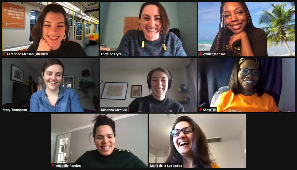 A screencap of a LivableStreets staff zoom call. Clockwise from the top left: Catherine Gleason, a young white woman with shoulder-length brown hair, leans her face on her hand; Lorraine Fryer, a white woman with chin-length brown hair falling in front of the left side of her face; Ambar Johnson, a Black woman with dark hair in long braids, leans her chin on the back of her hand; Shavel'le Olivier, a young Black woman with glasses and straight, shoulder-length dark hair held back by a hairband; María de la Luz Lobos Martinez (Luli), a young white Latina woman with glasses and long dark brown hair with streaks of purple; Anabelle Rondon, a Latina woman with her hair pulled back into a casual bun; Stacy Thompson, a white woman with dark brown hair in a pixie cut; and in the center, Kristiana Lachiusa, a white woman with brown hair wearing large over-ear headphones. Everyone has a big smile showing their teeth.