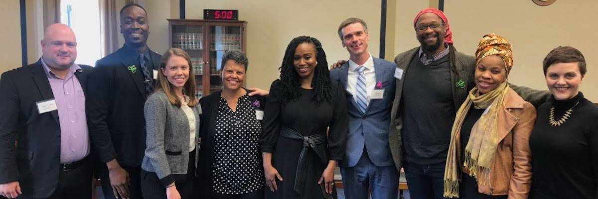 Banner image for the policy page, showing a row of 9 people standing together and smng at the camera. Among these people are Representative Ayanna Pressley and LivableStreets Executive Director Stacy Thompson.