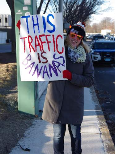 A blonde white woman in a long coat, winter hat, and orange sunglasses stands on a sidewalk holding a sign that reads \