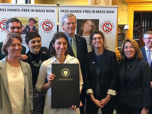 Vision Zero coalition members stand with Charlie Baker, holding the hands-free bill that he had recently signed