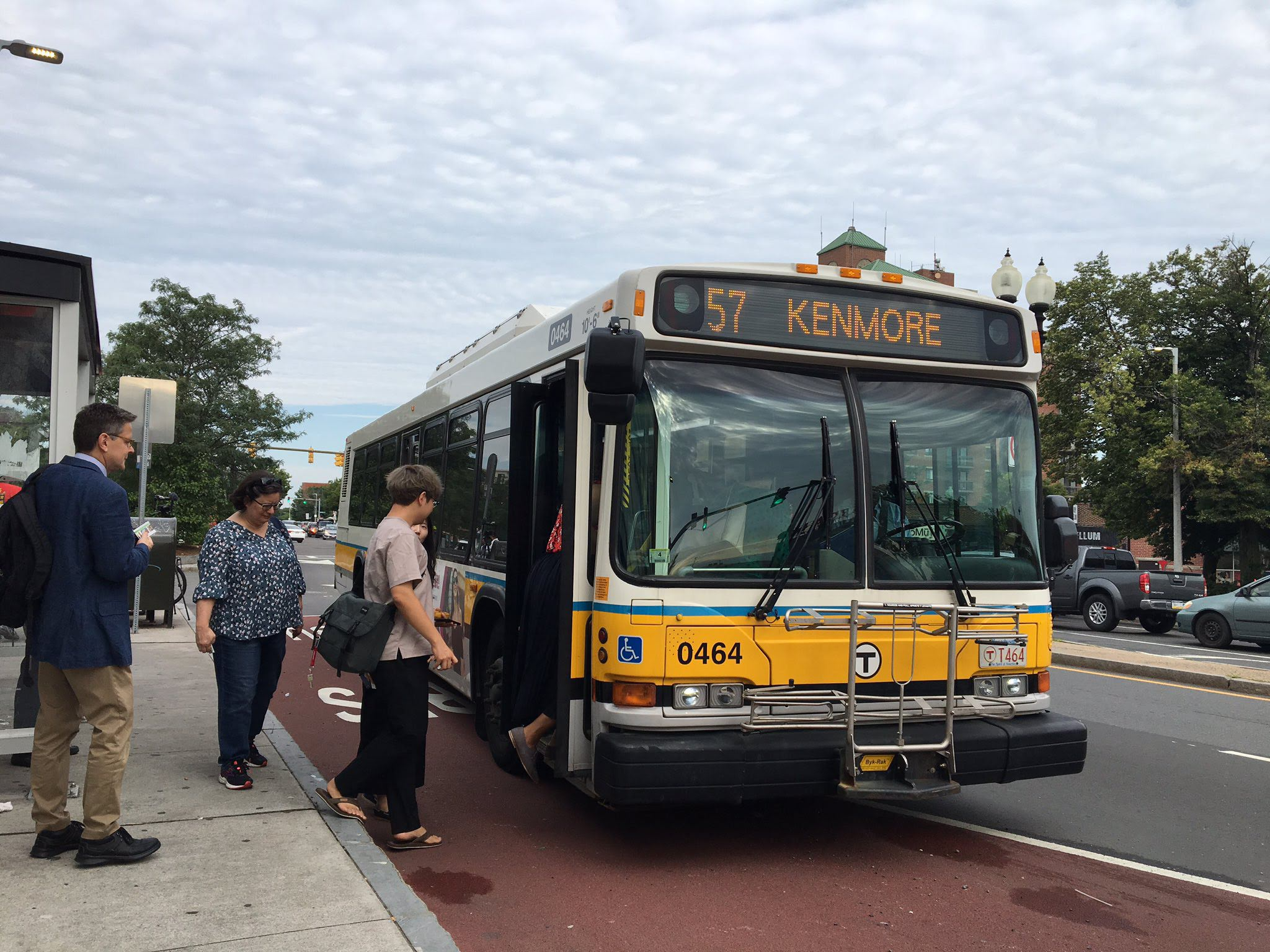 a line of people board a 57 bus to Kenmore Square. The bus sits in a red bus-bike only lane.