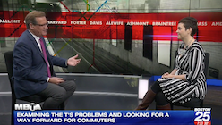 "A man and a woman sit in chairs facing each other; at the bottom of the screen is the text ""examining the t's problems and looking for a way forward for commuters"""