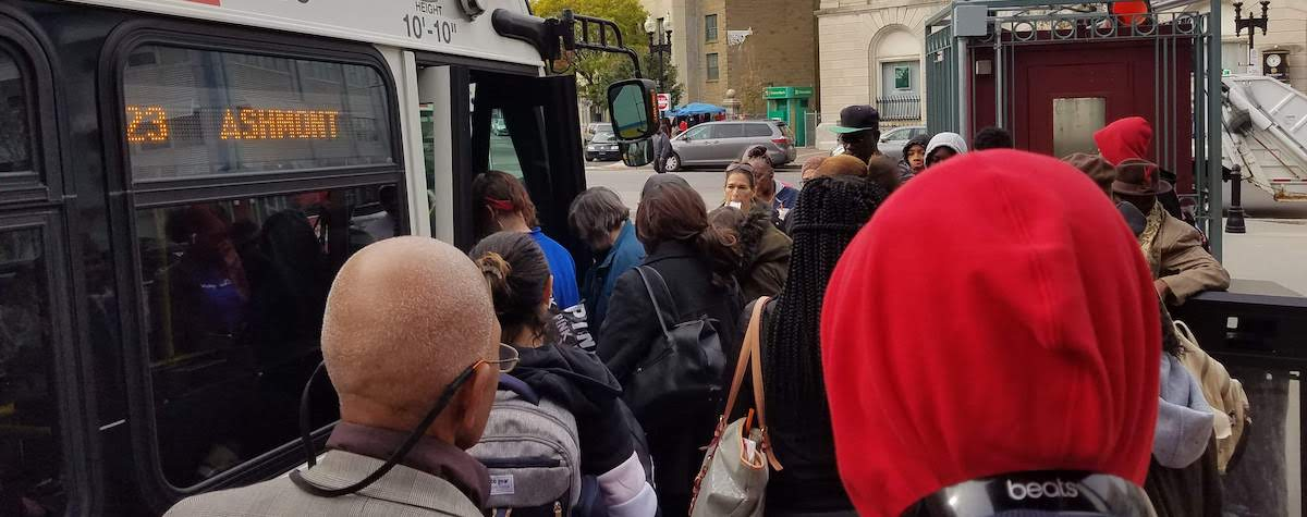 A large crowd of people stand outside a 23 bus to Ashmont, waiting to board.