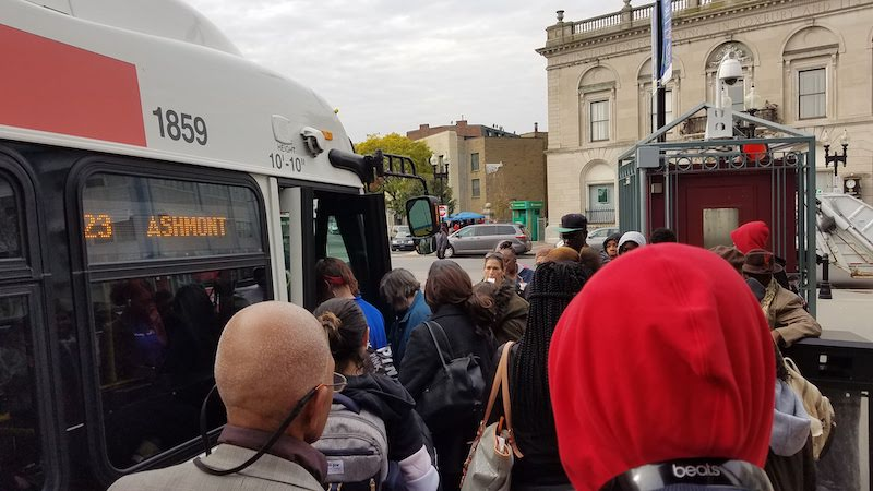 A crowd of people stand outside a 23 bus to Ashmont, waiting to board.