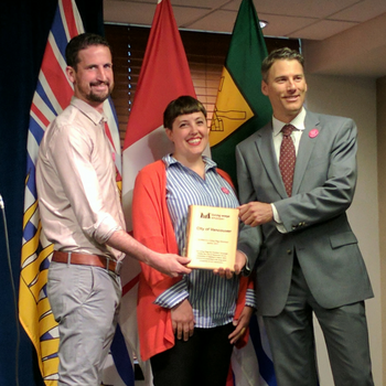 Park Board Chair Michael Wiebe and Mayor Gregor Robertson hold the Living Wage Employer plaque. Campaign Organizer, Deanna Ogle stands in the middle. Everyone is smiling.
