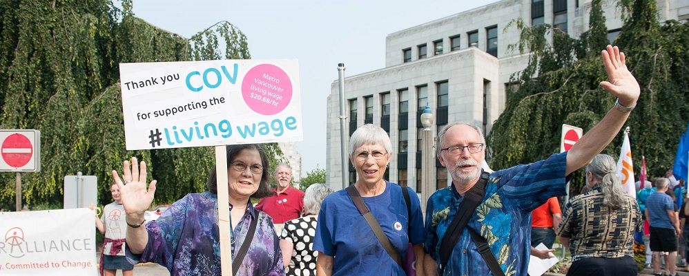 Three individuals stand in front of the City of Vancouver City Hall holding a sign that reads thank you COV for supporting the living wage