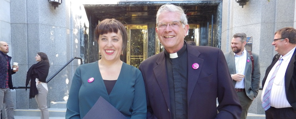 Deanna Ogle, Campaign Organizer and Steve Bailey, Deacon of the New Westminster Diocese of the Anglican Church stand in front of Vancouver City Hall