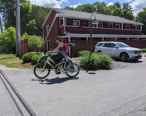 Woman riding a white e-bike on a road in Stowe, Vermont