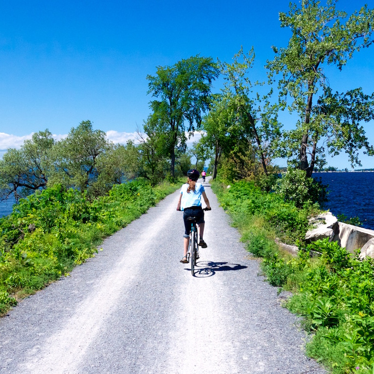 A kid biking on the Colchester Causeway in the middle of Lake Champlain with trees lining the edge of the trail