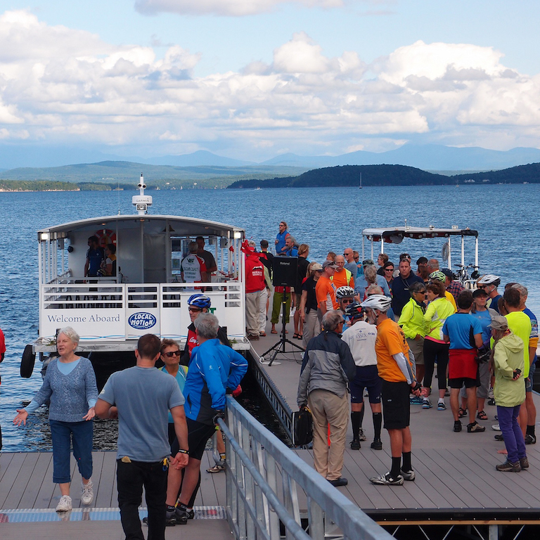 Crowds of people at the Bike Ferry dock waiting to board to cross the Colchester Causeway \