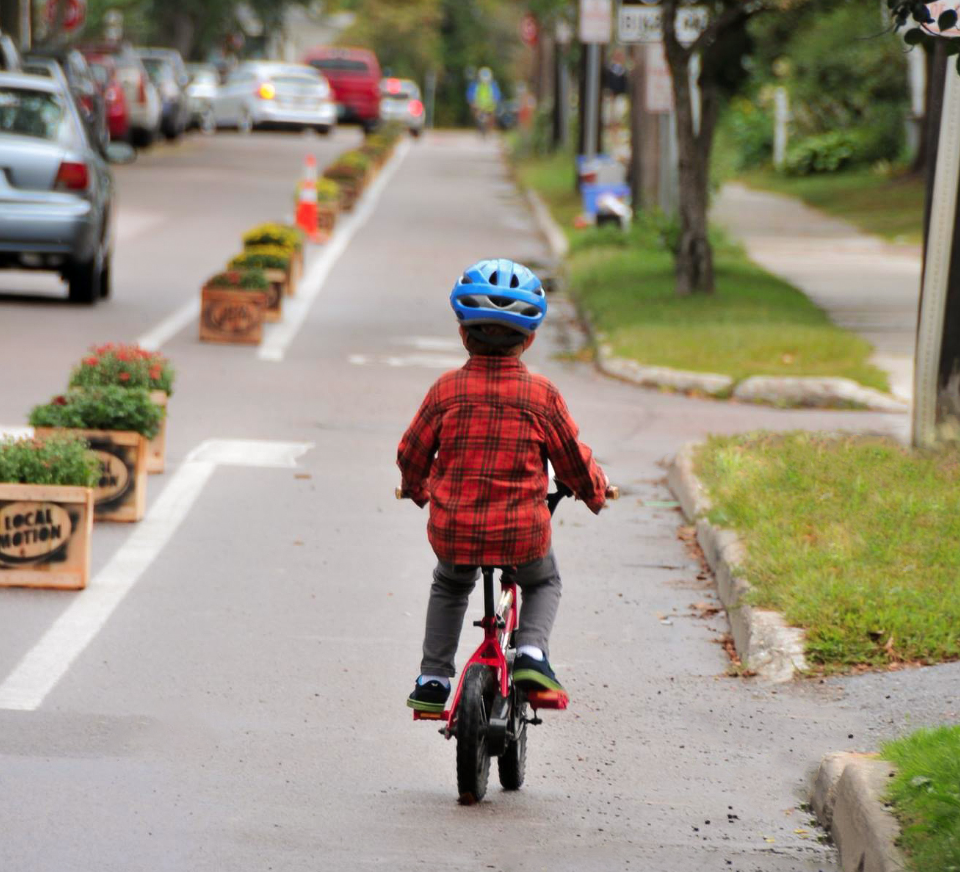 A kid in a red flanel bikes down a protected bike lane in Burlington, Vermont
