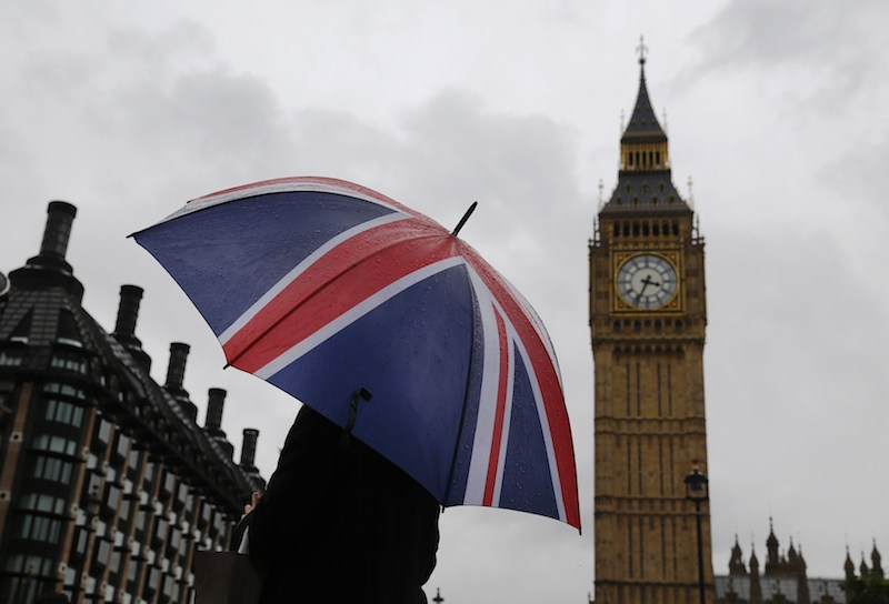 A woman holds a Union flag umbrella in front of the Big Ben clock tower and the Houses of Parliament in London