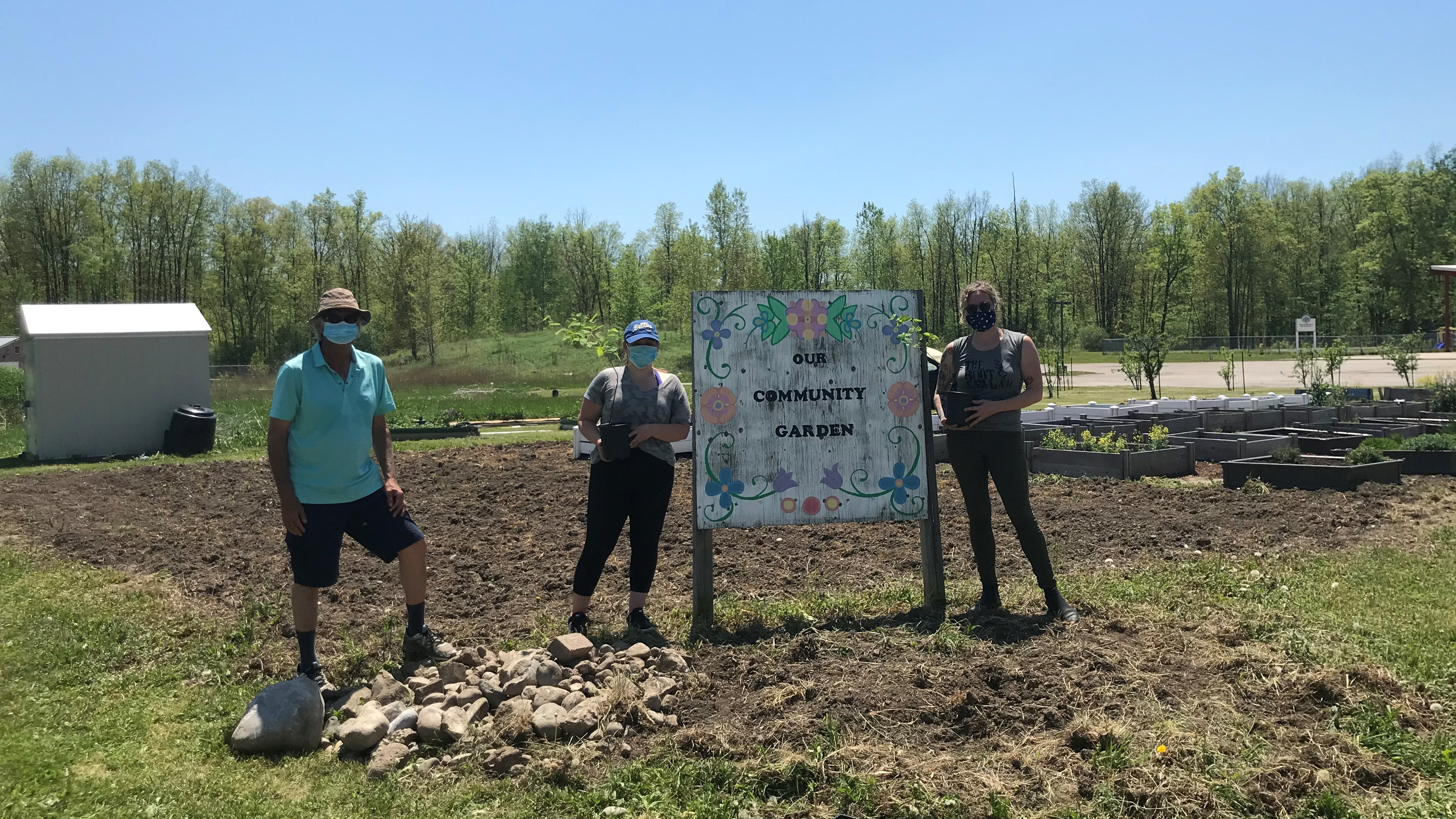 Three people standing at the community garden at Chippewas of the Thames First Nation