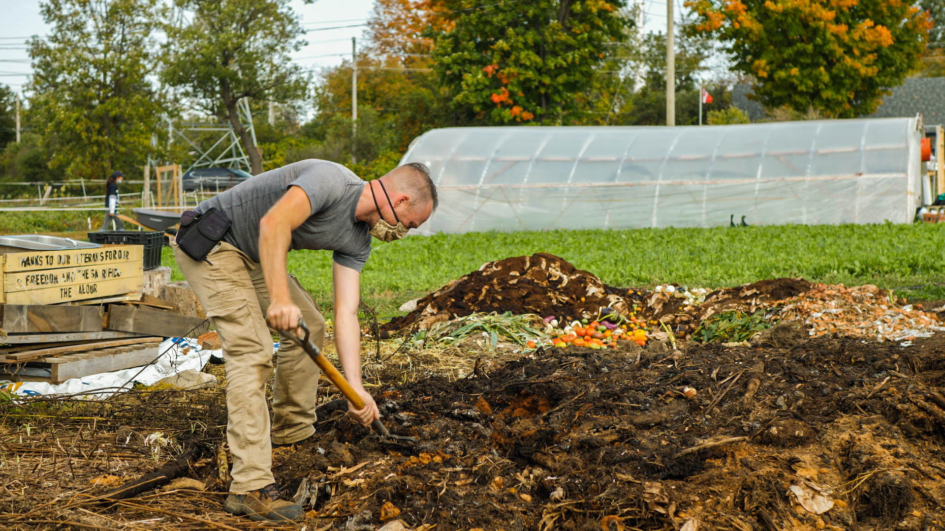 On-farm Manager, Denis shovels the compost material from their Community Compost Program to aerate the pile.