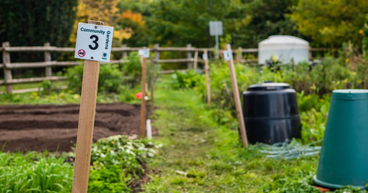 A close up of a community garden plot sign, with more garden blots and compost bins in the background.