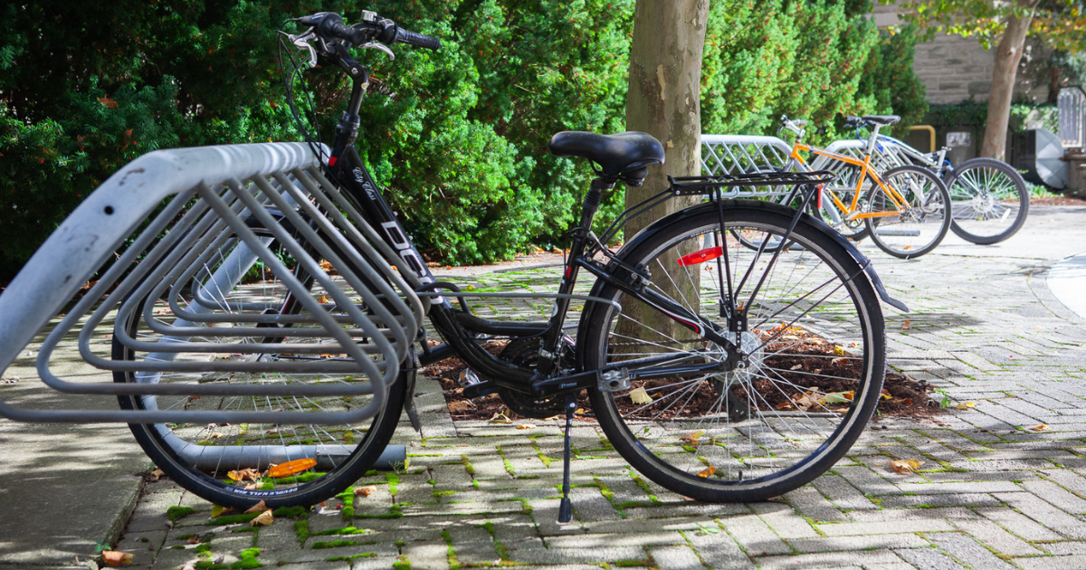 A bike is locked to a bike rack, with another bike rack off in the background.