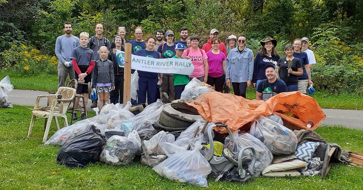Volunteers stand beside the garbage collected at a river clean-up