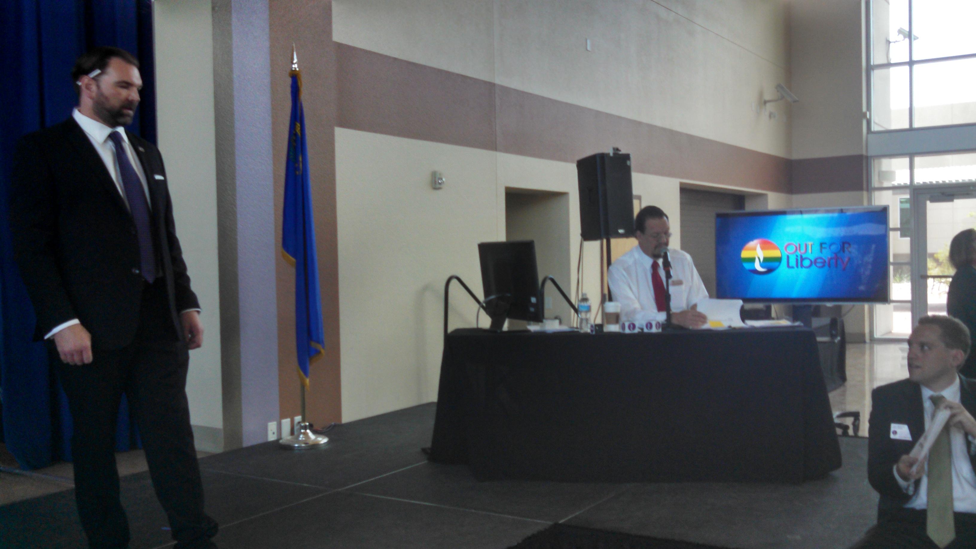 LP Nevada chair Brett H. Pojunis talks logistics with Jason Weinman as Penn prepares to moderate the debate. Photo by Zach Foster.