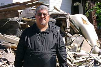 Luis J. Rodriguez in front of what was once someone's home