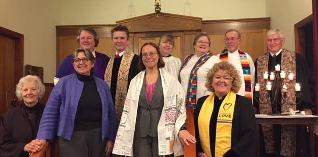 Group of clergy members standing together in front of a church podium and smiling