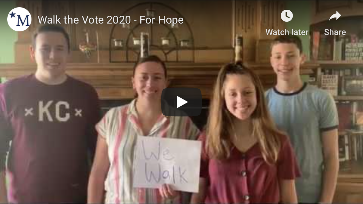 Snapshot of video with four kids holding signs