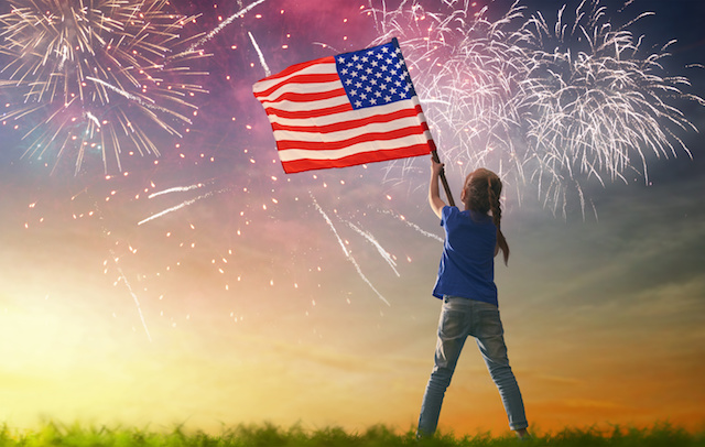 Girl with American flag and fireworks