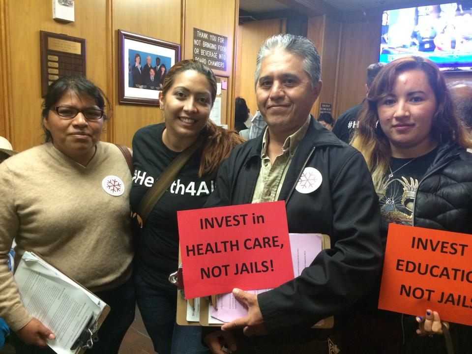 Two ACCE members holding up signs that demand that we invest in health care and education, instead of jails.