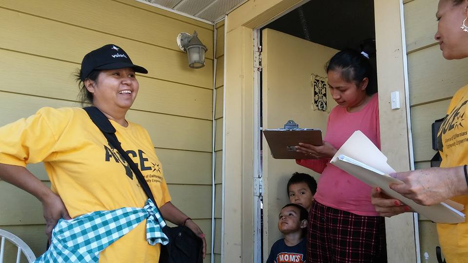 ACCE member talks to voter at their door, while voter fills out a count on me form.