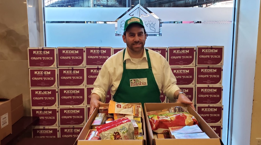 Masbia kosher supervisor assembles boxes containing food for people who may be quarantined or unable to obtain food due to the coronavirus outbreak.