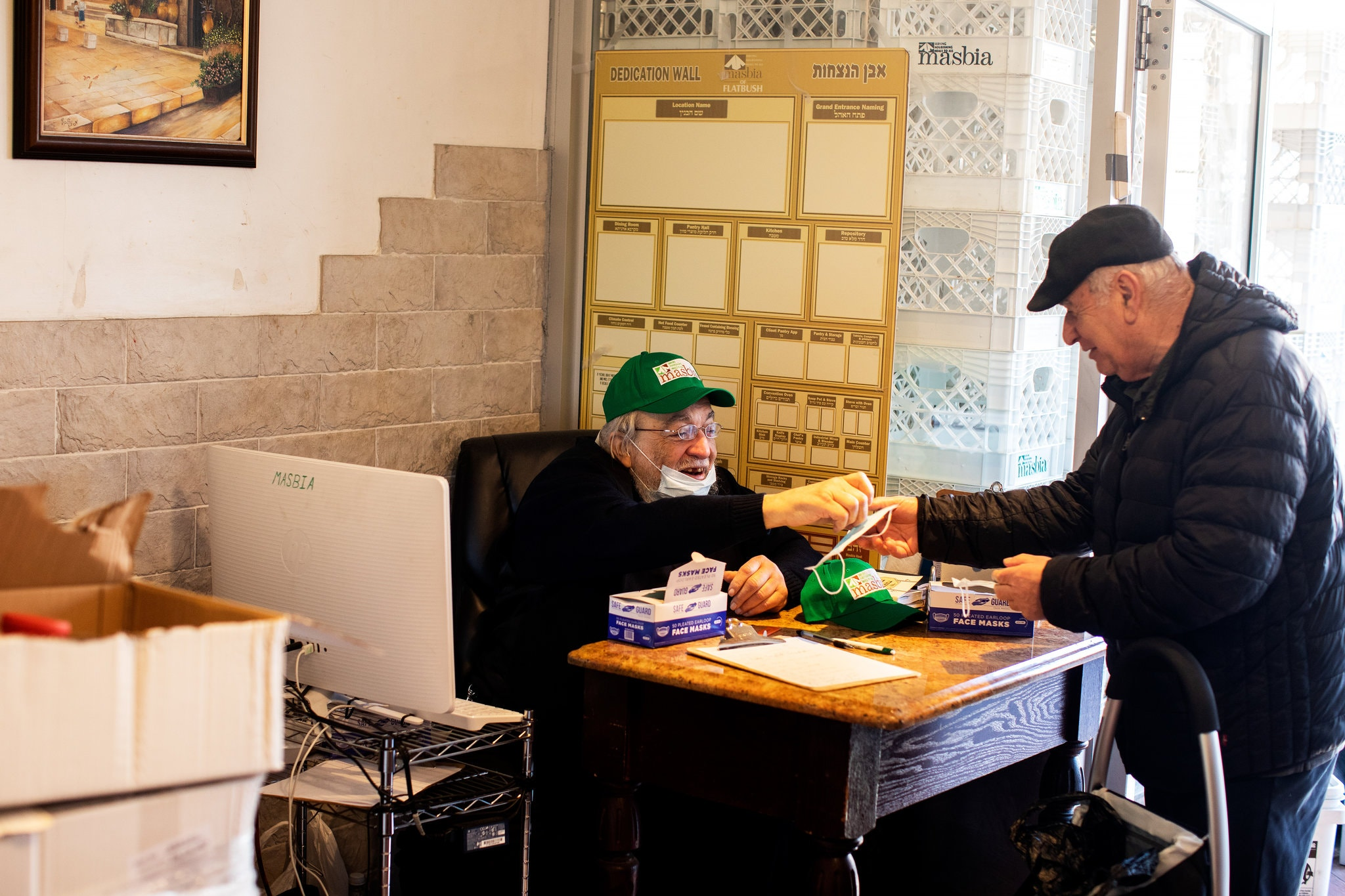 A Masbia volunteer handing a client a mask and checking him in.