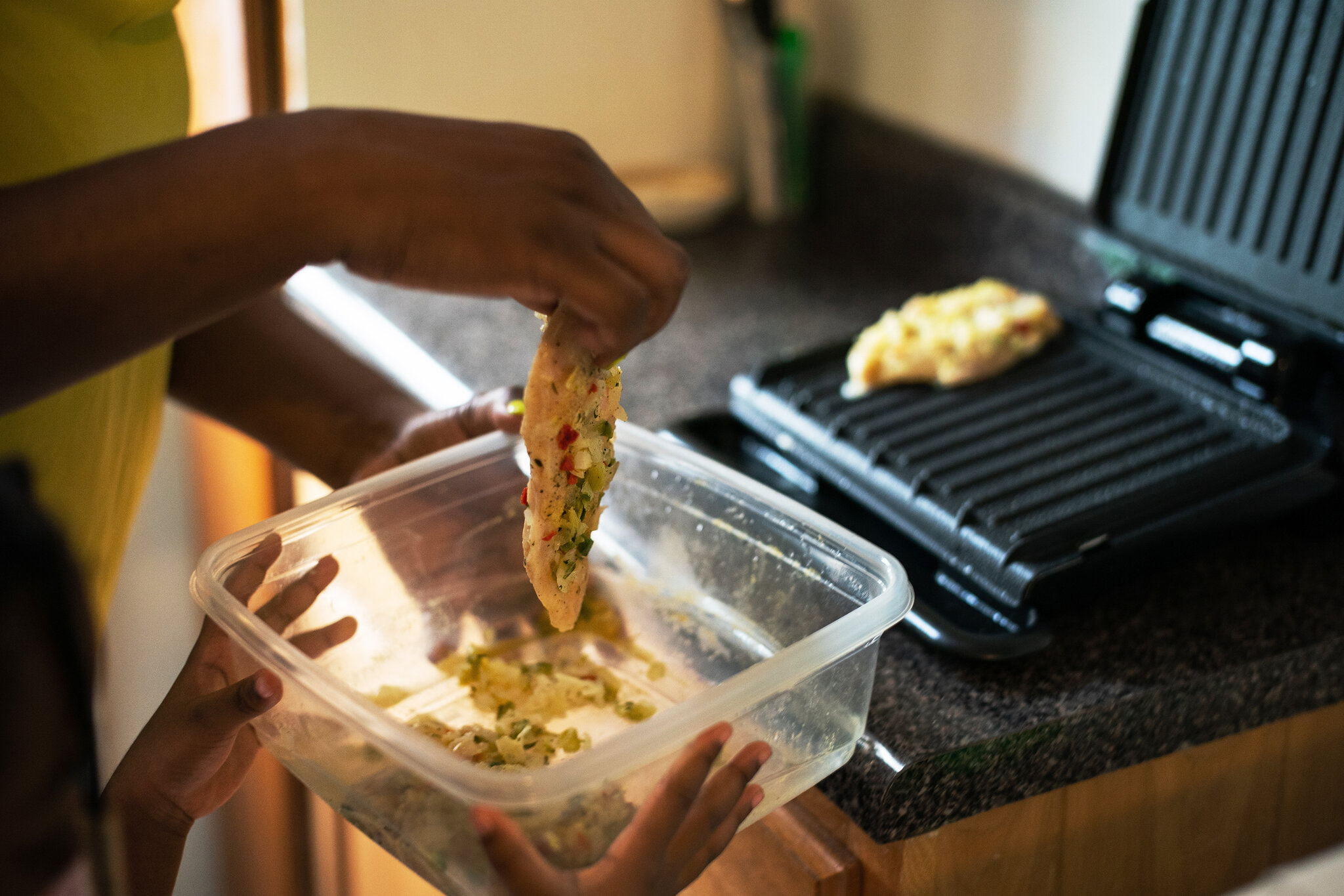 Leslie prepares delicious chicken cutlets thanks to nonprofit organizations such as Masbia in Brooklyn have a decent meal on their table. Photo by Todd Heisler.