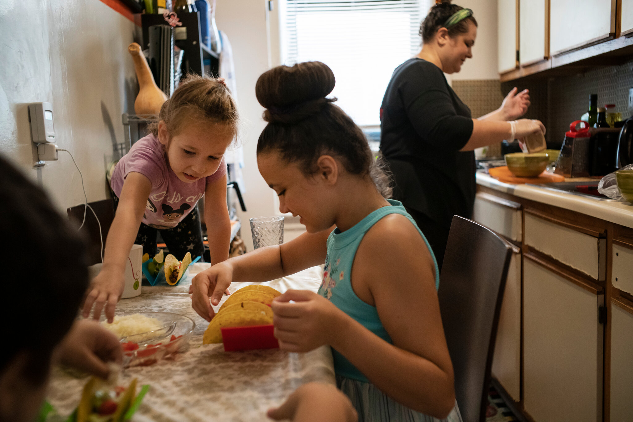 Yuliya and her little girls are very happy that Masbia Soup Kitchen Network share free food to make it possible to her prepare delicious meals. The photo was taken by Todd Heisler of the New York Times