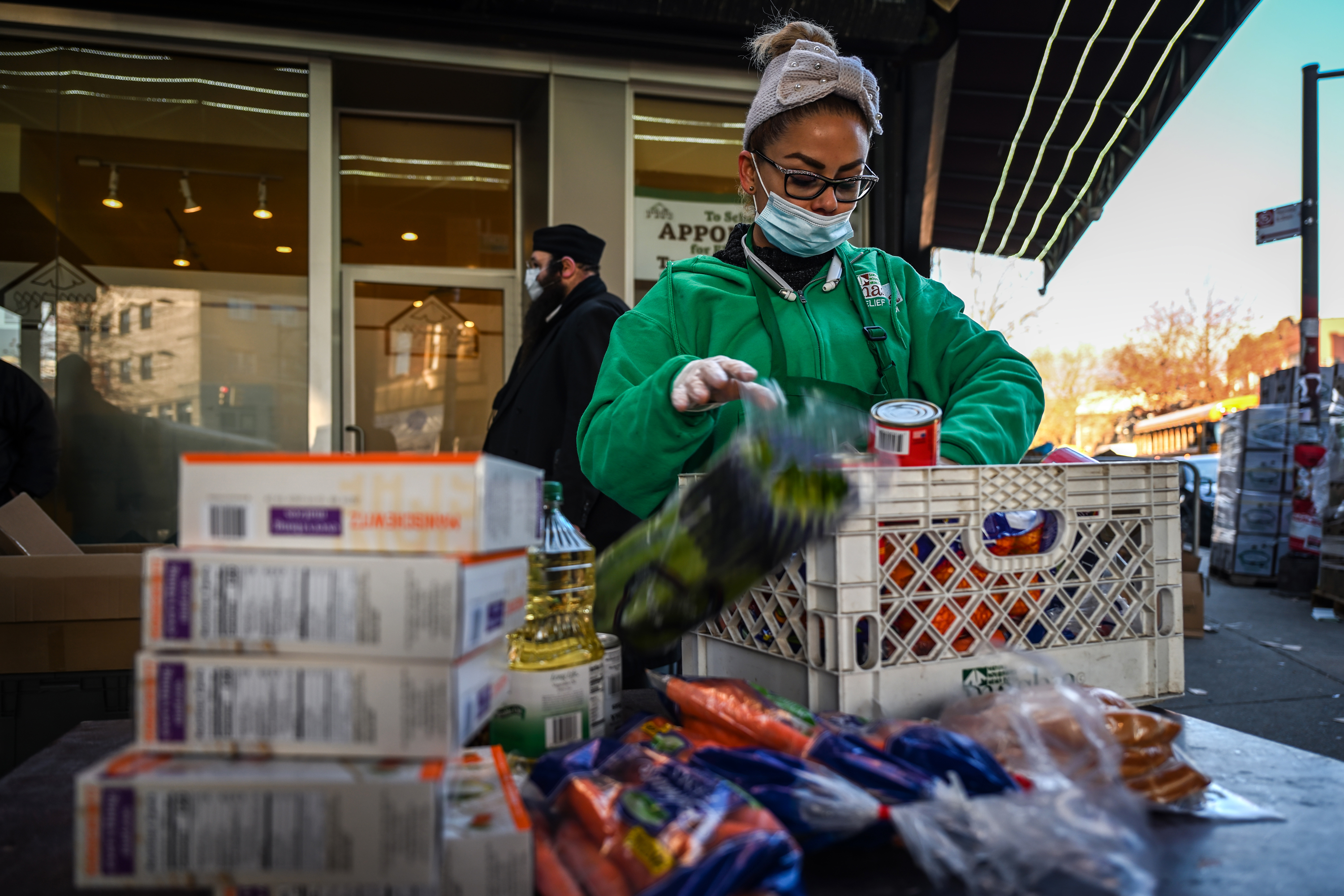 Worker Carolina Sanchez restocking food on the tables at Masbia pantry location