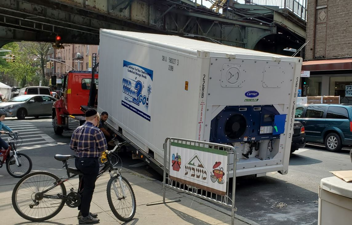 Driver unhitching the container from the truck at Masbia Soup Kitchen Network