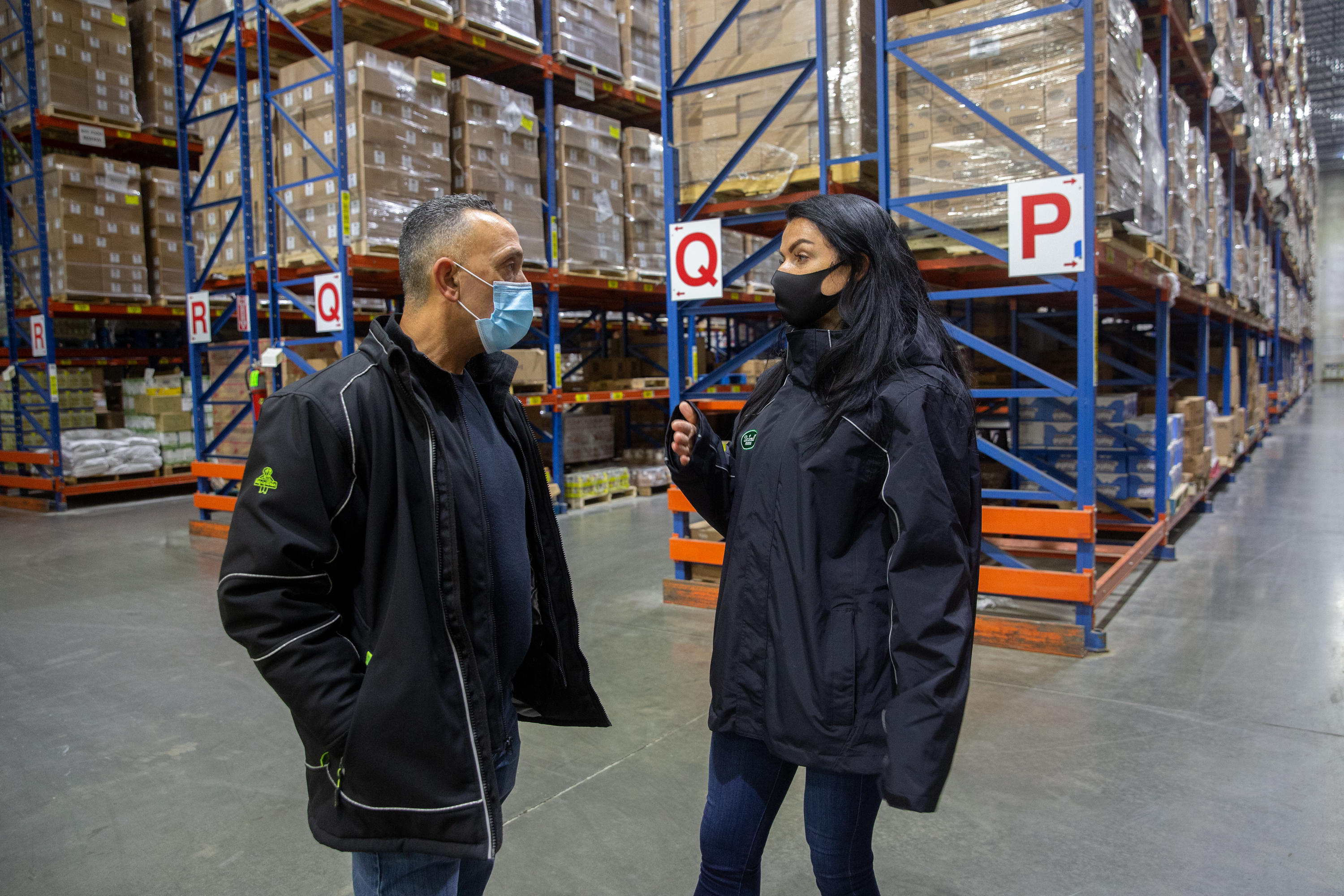 Warehouse manager Monte Santana speaks with VP of Operations Sara Kenyon in the warehouse stocked with food that soon will be delivered to nonprofit organizations like Masbia Soup Kitchen