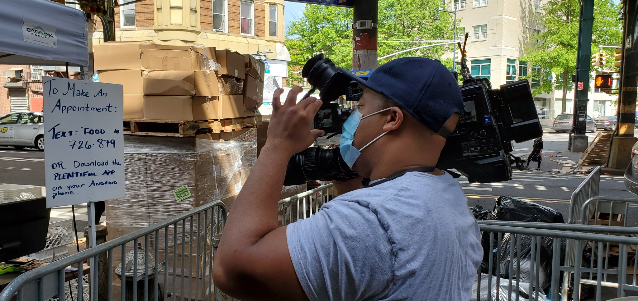 Reporter Christian L Braxton of News12 Brooklyn focusing his camera at Masbia of Boro Park during covid-19 pandemic