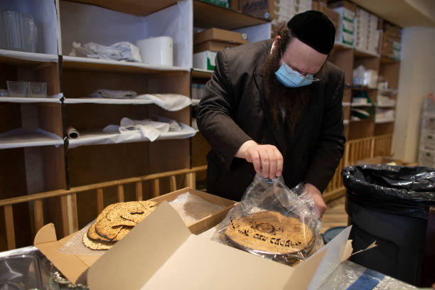 Alexander Rapaport ED  Masbia soup kitchen network  open a bag of matzah as workers prepare meals for the beginning of Passover celebrations